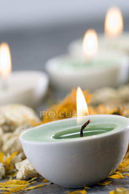 Close-up of lighting candle and dried flowers in spa — Stock Photo