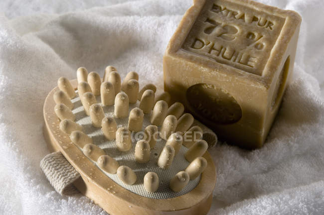 Close-up of soap and wooden massager on white towel — Stock Photo