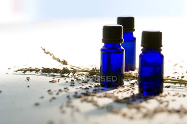 Close-up of blue essential oil bottles and dried grains — Stock Photo