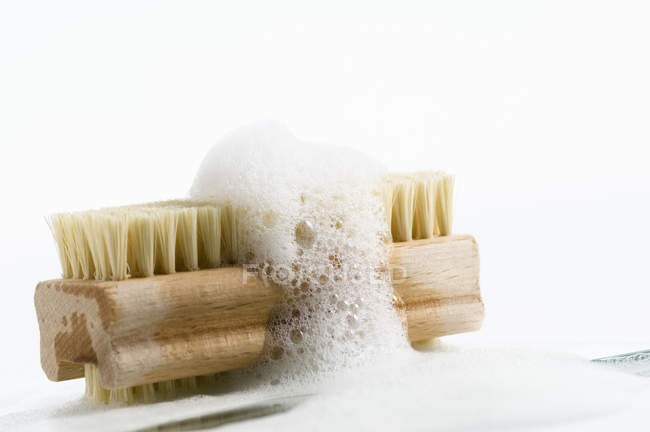 Close-up of Nail brush with soap foam on white background — Stock Photo