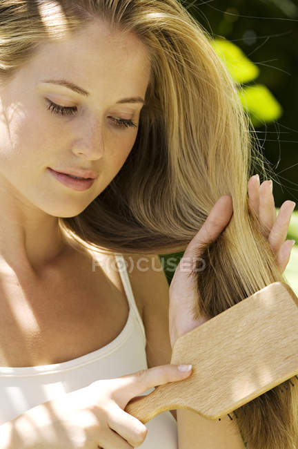 Portrait of young blond woman brushing hair outdoors — Stock Photo