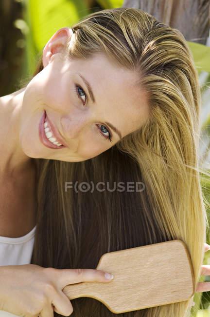 Портрет улыбающейся молодой женщины, расчесывающей волосы на улице — стоковое фото