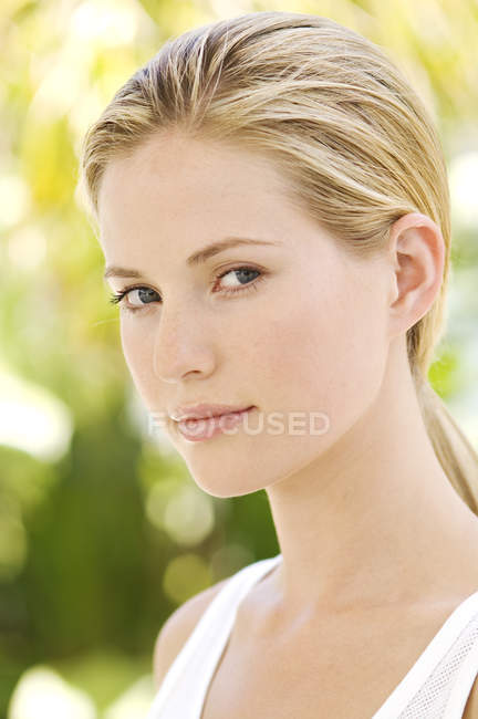 Portrait of young blond woman looking at camera outdoors — Stock Photo