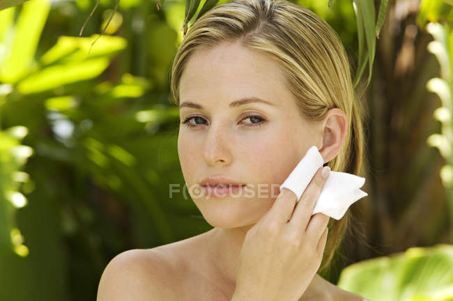 Portrait of young woman using cleansing cotton on face outdoors — Stock Photo