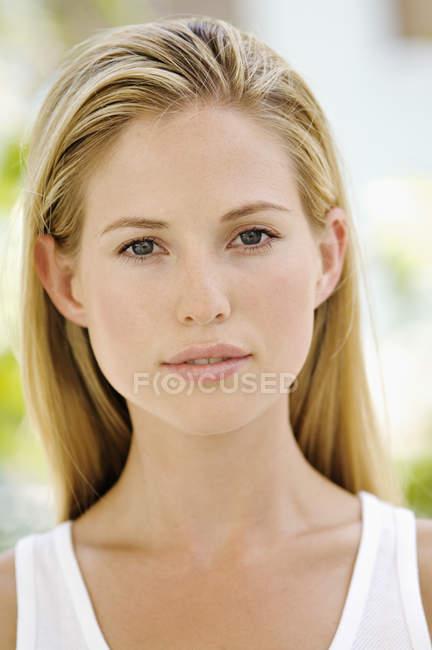 Portrait de jeune femme regardant la caméra à l'extérieur — Photo de stock