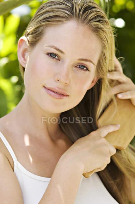 Портрет молодой женщины, расчесывающей волосы на улице — стоковое фото