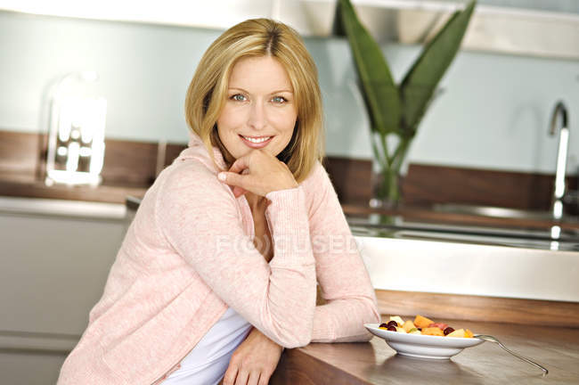 Smiling woman sitting at table with fruit salad in kitchen and looking at camera — Stock Photo
