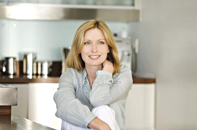 Lächelnde nachdenkliche Frau in der Küche sitzen und wegsehen — Stockfoto