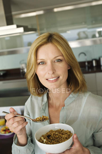 Ritratto di donna che mangia cereali in cucina — Foto stock
