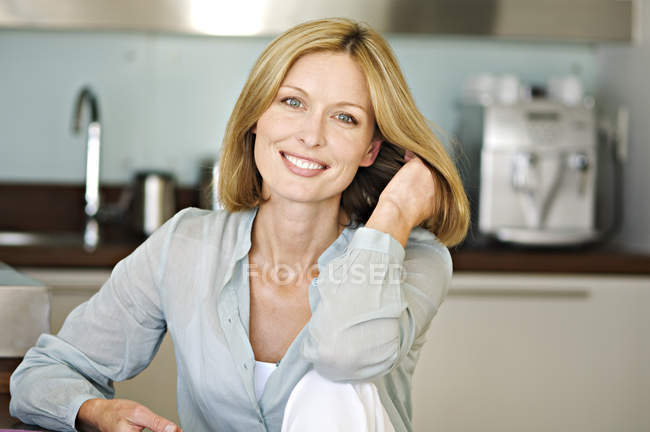Smiling woman with hand in hair looking at camera in kitchen — Stock Photo
