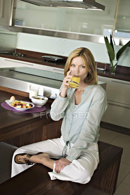 Donna che beve succo di frutta mentre si siede sulla panchina — Foto stock