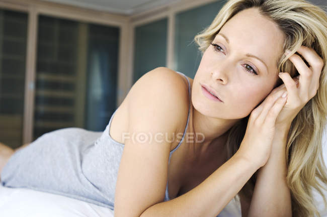 Young blonde thoughtful woman lying on bed — Stock Photo
