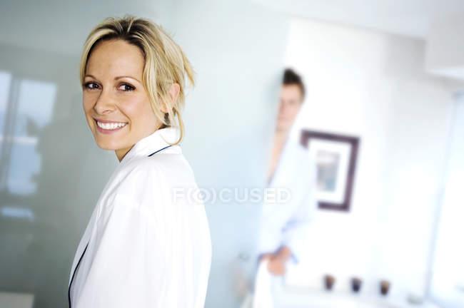 Портрет усміхнений молоду жінку в халат і людина на тлі — стокове фото