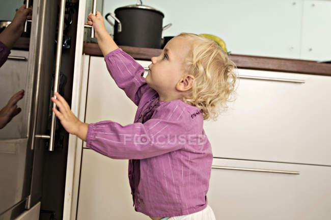 Menina abrindo geladeira na cozinha — Fotografia de Stock