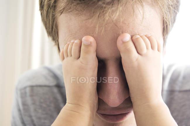 Primo piano del padre che gioca con i piedi del bambino sugli occhi — Foto stock