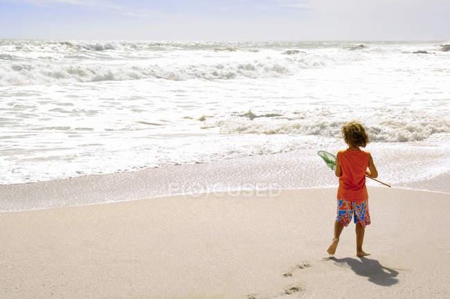 Маленький мальчик стоит на пляже и держит сетку для посадки — стоковое фото