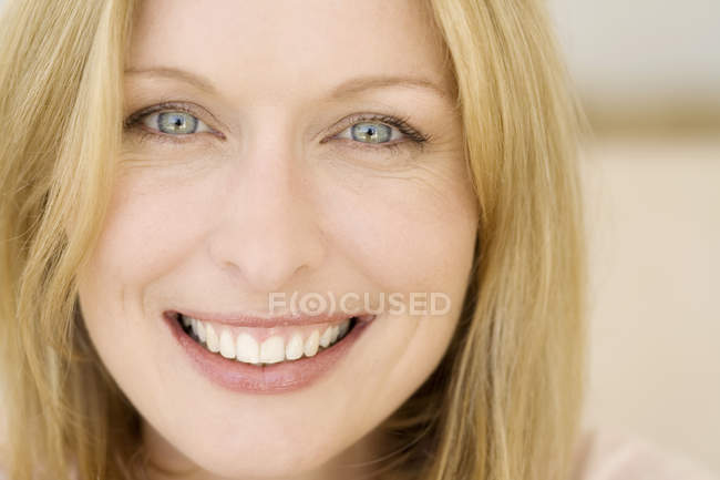 Portrait of blonde young smiling woman with blue eyes — Stock Photo