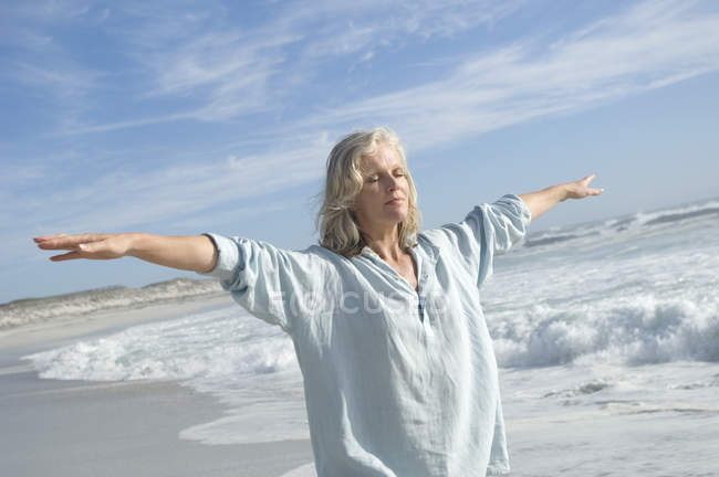 Woman with arms outstretched and eyes closed doing yoga on beach — Stock Photo