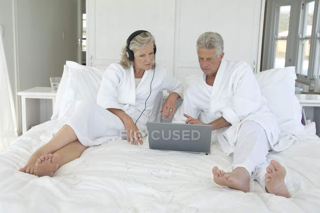 182af74ad2 Mature couple in bathrobes using laptop in bed — Stock Photo
