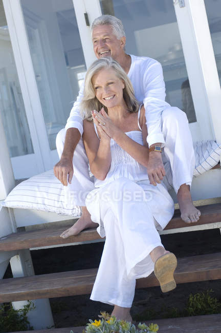 Smiling embracing couple embracing sitting on terrace stairs — Stock Photo