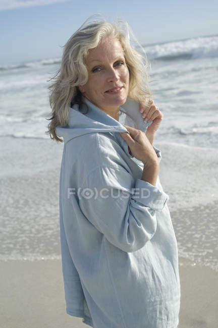 Mujer madura mirando a la cámara en la playa - foto de stock