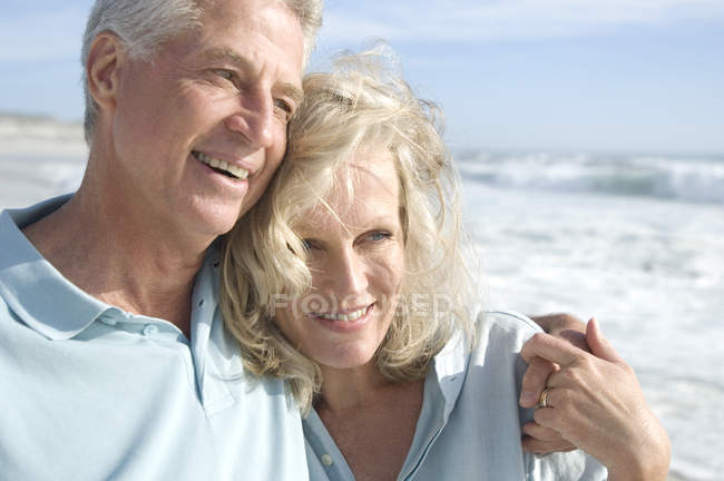 Portrait of smiling couple embracing on beach — Stock Photo