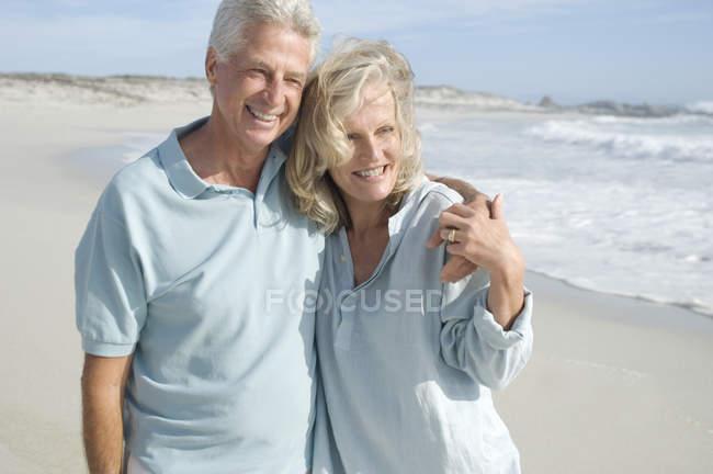 Улыбающаяся зрелая пара, обнимающаяся на песчаном пляже — стоковое фото