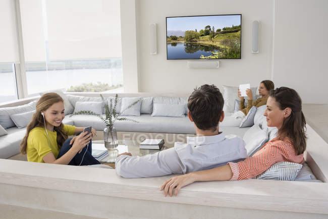 Par ver la televisión con hijas con gadgets - foto de stock
