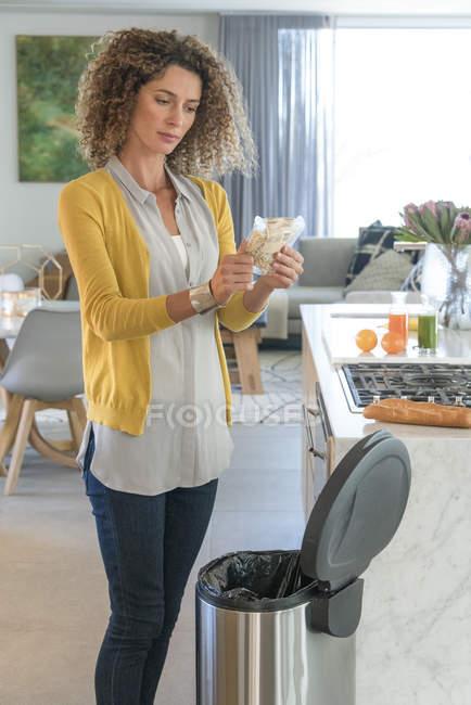 Frau wirft Beutel von Lebensmitteln in Mülltonne in Küche — Stockfoto