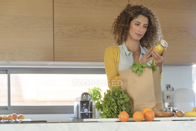 Frau hält Glas mit Essiggurken in Küche — Stockfoto