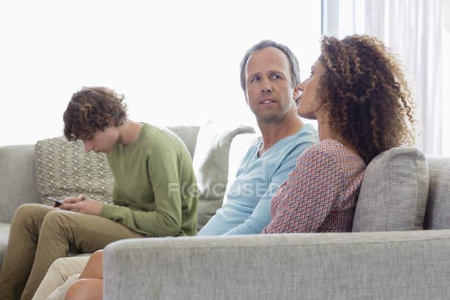 Coppia che si siede sul divano e parlando con il figlio che per mezzo del telefono mobile su priorità bassa nel salotto a casa — Foto stock