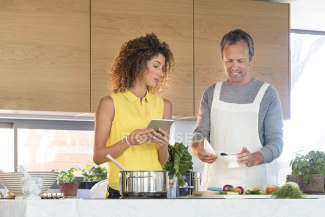 Пара готовит еду на кухне с цифровым планшетом — стоковое фото