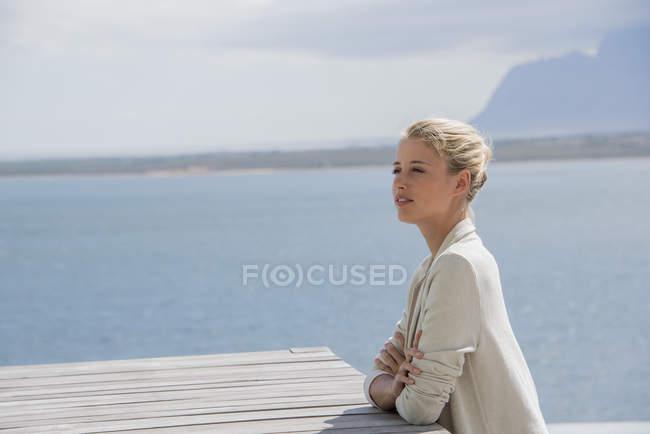 Элегантная молодая женщина сидит за столом на берегу озера и смотрит в сторону — стоковое фото