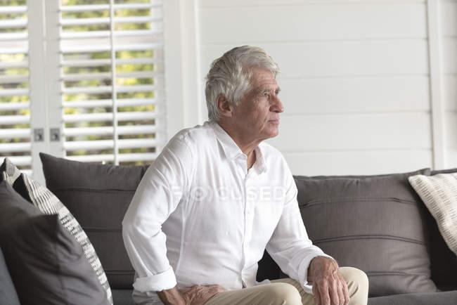 Nachdenklicher senior Mann sitzt zu Hause auf sofa — Stockfoto