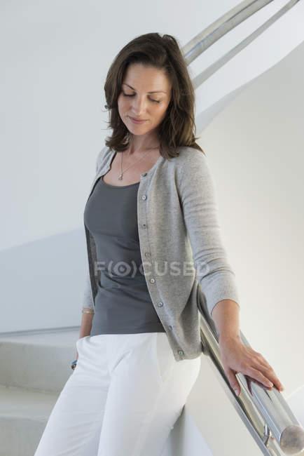 Nachdenkliche reife Frau, die auf der Treppe steht und nach unten schaut — Stockfoto