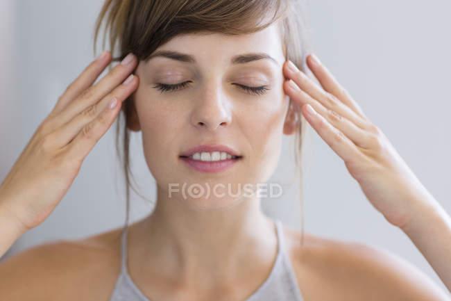 Femme, toucher des temples avec doigts sur fond gris — Photo de stock