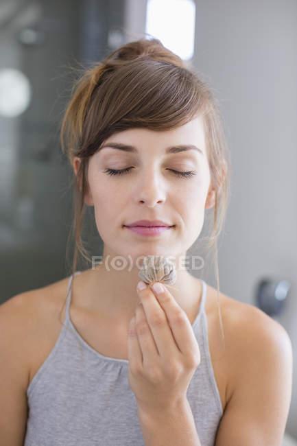 Primo piano della giovane donna che sente odore di bustina di tè — Foto stock