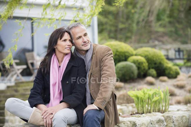 Романтична пара вдумливі, сидячи в саду і дивитися вбік — стокове фото
