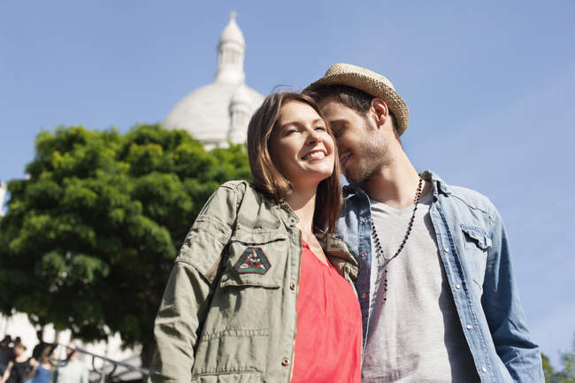 Low angle view of smiling couple standing in city together — Stock Photo
