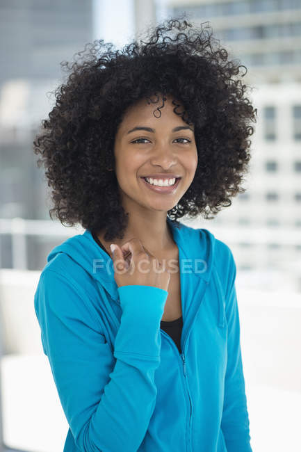 Portrait of smiling woman with afro hairstyle in blue hooded top — Stock Photo
