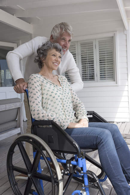 Happy senior man assisting wife in wheelchair on porch — Stock Photo