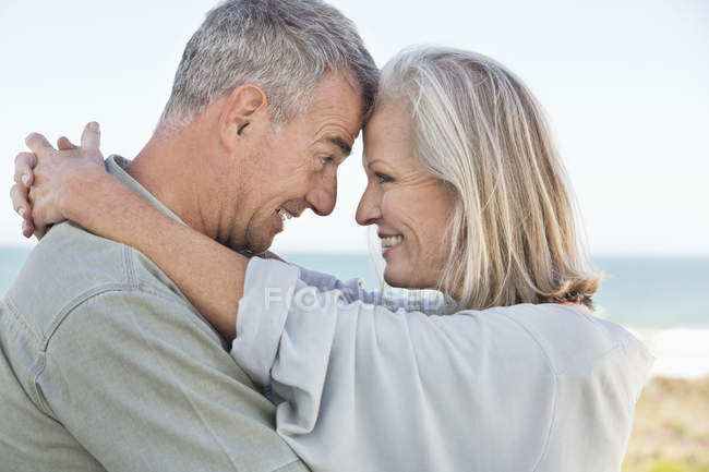 Romantic happy couple standing on beach and looking at each other — Stock Photo