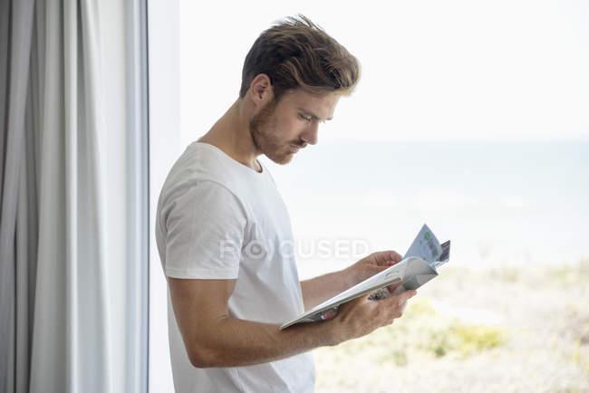 Young man reading magazine against glass window — стокове фото