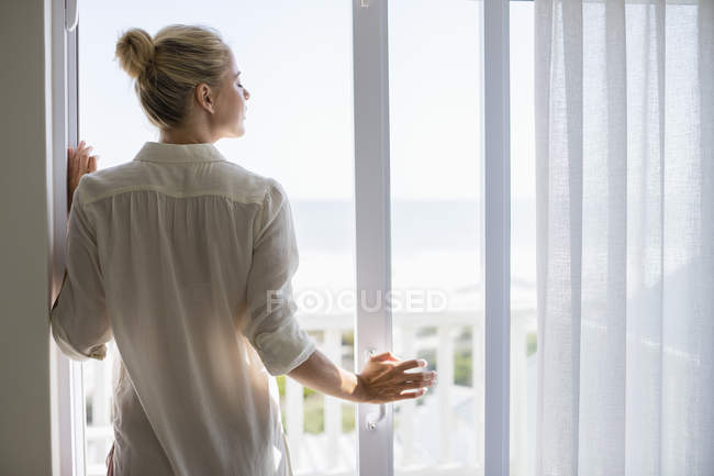 Relaxed young woman standing at window at home — Stock Photo