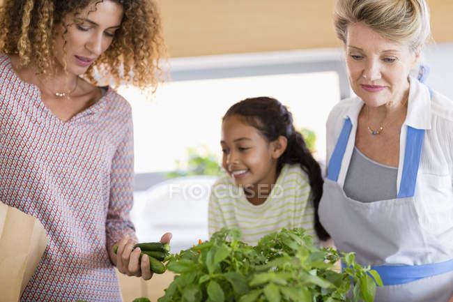 Старші жінки з дочку і онука, дивлячись на зелень і овочі кухні — стокове фото
