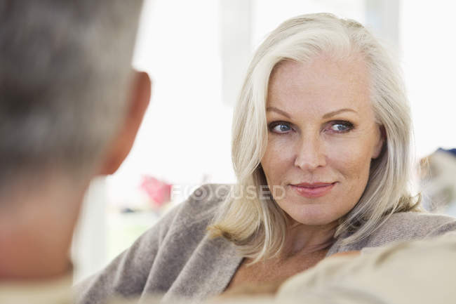 Close-up of thoughtful senior woman sitting with husband on sofa at home — Stockfoto