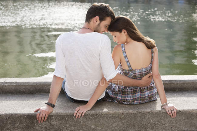 Rückansicht eines Paares, das am Kanalrand sitzt — Stockfoto