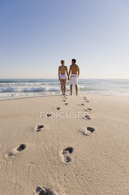 Footprints on sandy beach with couple standing on background and looking at view — Stock Photo