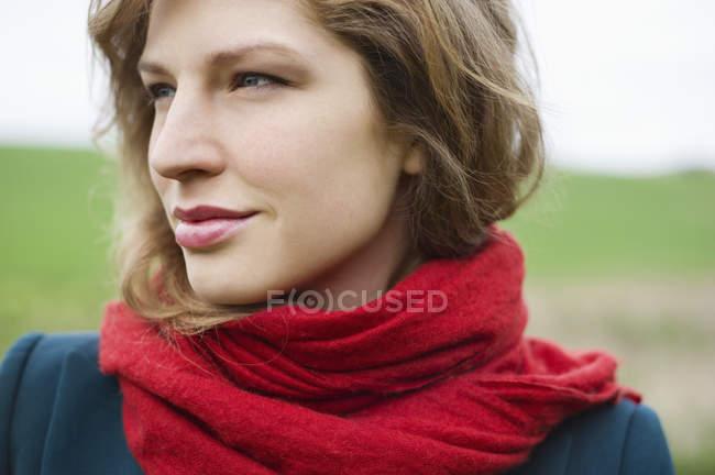Молода жінка в червоних шарф мрій в поле — стокове фото
