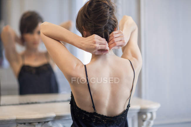 Elegant woman putting on necklace in front of mirror — Stockfoto
